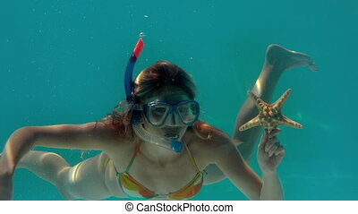 Woman wearing snorkel holding starfish underwater in slow...