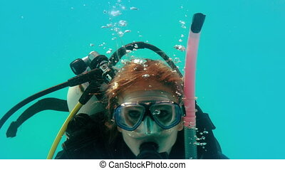 Woman in scuba gear looking at camera underwater in slow...