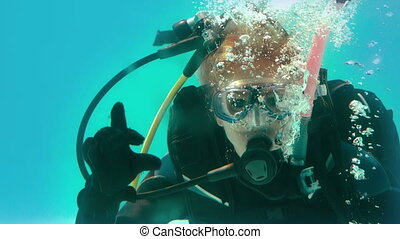 Woman in scuba gear looking at camera underwater making ok...