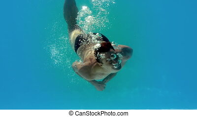 Fit man spinning around underwater in swimming pool in slow...