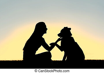 Woman and Dog Shaking Hands Sunset Silhouette - A silhouette...