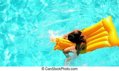 Brunette splashing on lilo in the swimming pool in slow...