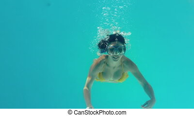 Gorgeous brunette in yellow bikini swimming underwater...