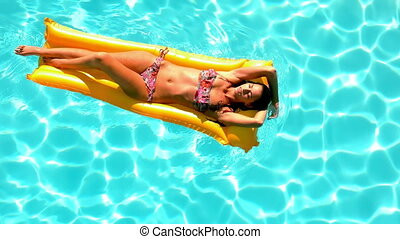 Brunette floating across the pool on lilo on sunny day in...