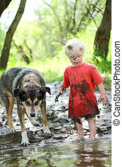 Young Child and Dog Playing in Muddy River - A young boy...