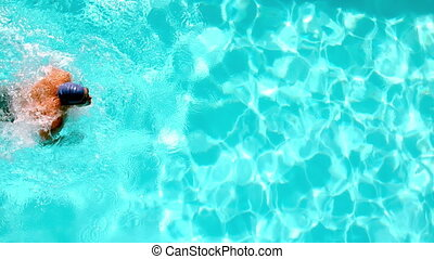 Athletic swimmer swimming across the pool overhead in slow...