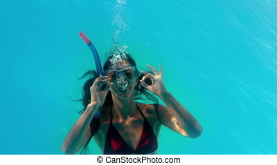 Brunette swimming underwater in the pool wearing snorkel in...