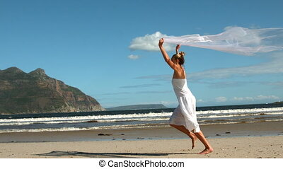 Carefree blonde running on the beach holding scarf up in...