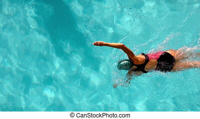 Fit female swimmer doing the front stroke in the swimming...