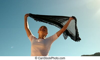 Happy woman holding black scarf above head on sunny day in...