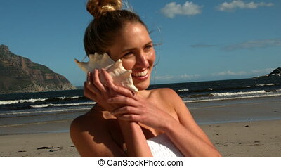 Smiling blonde listening to conch on the beach in slow...