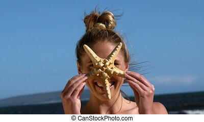 Smiling blonde holding up starfish on the beach in slow...