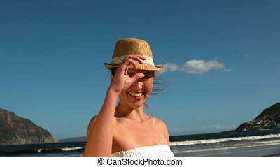 Smiling blonde taking off her sunhat on the beach in slow...