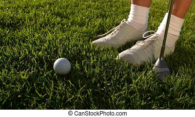 Golf ball falling beside lady golfers feet and club in slow...