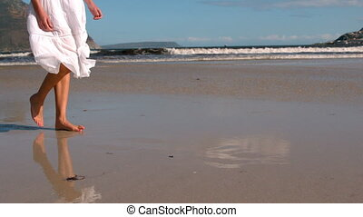 Woman in white dress walking on the beach - Woman in white...