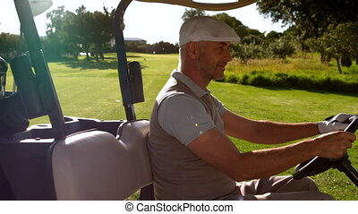 Happy golfer driving buggy on the course - Happy golfer...