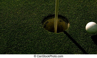 Golf ball rolling into the hole on