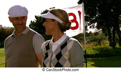 Golfing couple smiling at the eighteenth hole on the golf...