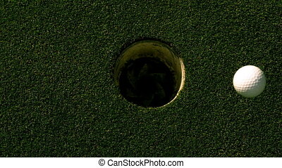 Golf ball rolling into the hole on putting green in slow...