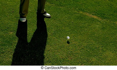 Golfer hitting the golf ball with club on the course in slow...