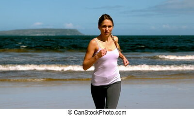 Fit blonde jogging on the beach in slow motion