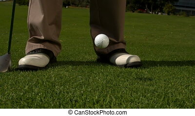 Golf ball falling beside golfers feet and club in slow...