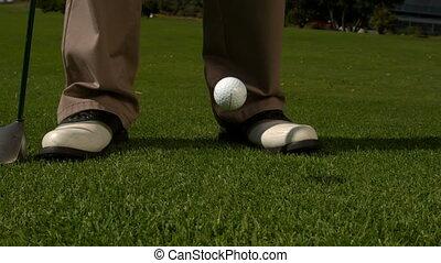 Golf ball falling beside golfers feet