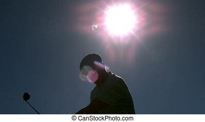 Golfer taking a swing under the sun in slow motion
