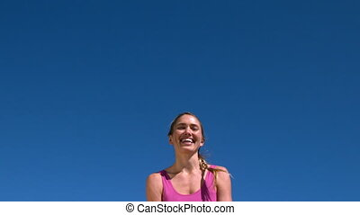 Fit blonde smiling and jumping up on sunny day in slow...