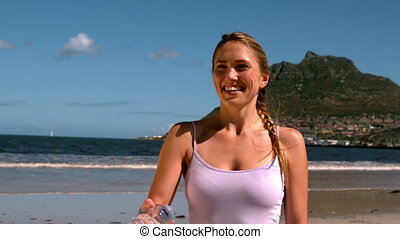 Fit blonde smiling and throwing her bottle on the beach in...