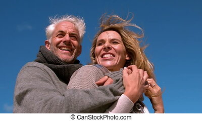 Carefree mature couple hugging on sunny day in slow motion