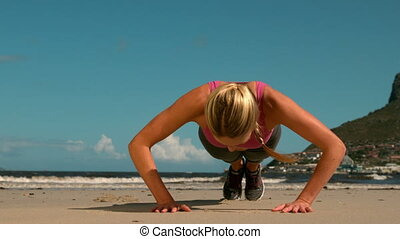 Fit blonde doing push ups on the beach in slow motion