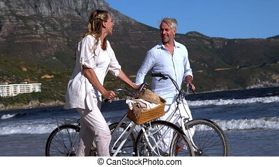 Carefree couple walking on the beach with their bikes in...
