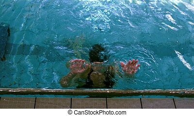 Fit swimmer emerging from pool and pulling herself up in...