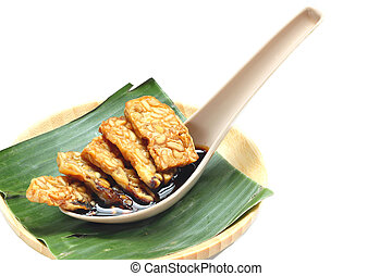 Fried tempeh for snack on banana leaf. Made by a natural...