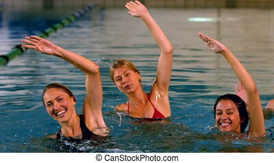 Happy fitness group doing an aqua aerobics class in slow...