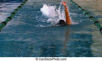 Fit female swimmer doing the back stroke in swimming pool in...