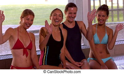 Happy group of women sitting poolsi