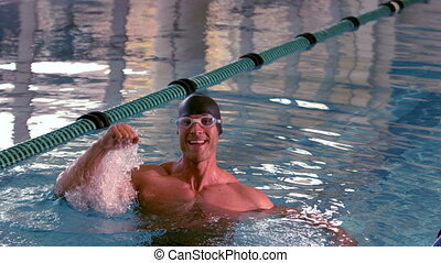Fit happy swimmer jumping up and cheering in the pool in...