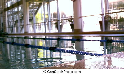 Fit swimmer emerging from pool and pulling himself up in...