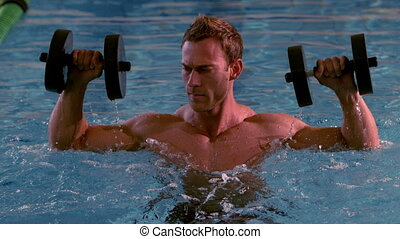 Muscular man working out with foam dumbbells in the pool in...