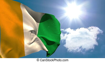 Ivory coast national flag waving on blue sky background with...