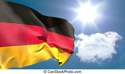 German national flag waving on blue sky background with sun...