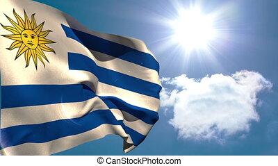 Uruguay national flag waving on blue sky background with sun...