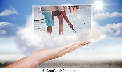 Hand presenting beach and holiday clips on blue sky...