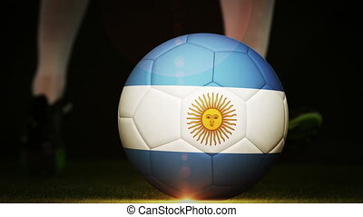 Football player kicking argentina flag ball on black...