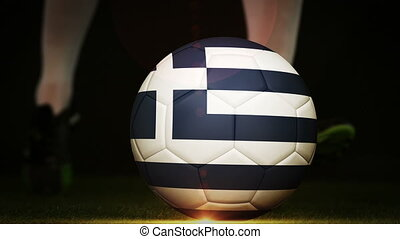 Football player kicking greece flag ball on black background...