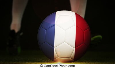 Football player kicking france flag ball on black background...