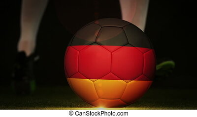 Football player kicking germany flag ball on black...