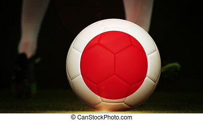 Football player kicking japan flag ball on black background...